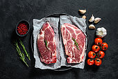 Fresh pork steak. Marbled meat. Black background. Top view