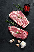Raw pork steak on the bone. Grilled meat. Black background. Top view