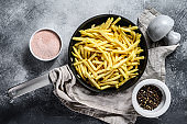 French fries in a frying pan. Gray background. Top view