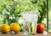 Set of glass full of water and melting ice and fresh fruits, close up view. Lemons, apple and glass with ice cubes on brown desk. Greenth on background. Selective soft focus. Blurred background.