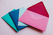 Colored paper envelopes on a light background. New mail, write message. Send and receive letter. Postal delivery service. Blank envelope, empty space. People communication, paperwork. Envelope closeup