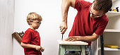 The father shows the little son how to tighten the screws with a screwdriver.