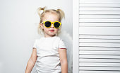 Children's fashion: a little girl in yellow sunglasses is posing seriously against a white wall, imitating a top model.