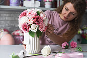Flower workshop: a florist girl makes bouquets of flowers in boxes to order.