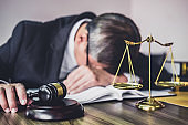 Judge gavel with lawyers, Gavel on wooden table and Counselor or Male lawyer is tired and migraine headaches during hard working on a documents at law firm. Legal law, advice and justice concept