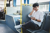 Young Asian man traveler sitting on a bus listening to music on smartphone while smile of happy, transport, tourism and road trip concept