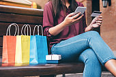 Consumerism, shopping, lifestyle concept, Young woman sitting near shopping bags and gift box while payment by smartphone enjoying in shopping