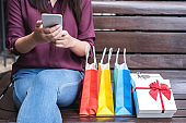 Consumerism, shopping, lifestyle concept, Young woman sitting near shopping bags and gift box while playing smartphone enjoying in shopping