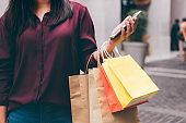 Consumerism, shopping, lifestyle concept, Young woman holding colorful shopping bags and smartphone enjoying in shopping