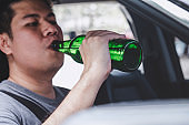 Young asian man drives a car with drunk a bottle of beer behind the wheel of a car