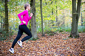Woman On Early Morning Autumn Run Through Woodland Keeping Fit Through Exercise