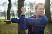 Woman Warming Up For Morning Exercise With Stretches In Winter Park