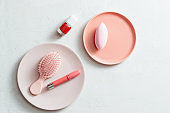Makeup products on pink plate on white background