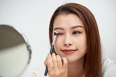 Close up of beautiful face of asian young woman getting make-up. Asian woman is applying eyeshadow on her eyebrow with brush. Beautiful girl look at mirror with hand make.