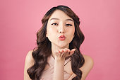 Beautiful young Asian woman blow a kiss on pink background