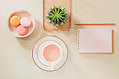 Styled stock photography beige office desk table with blank notebook, macaroon, supplies and coffee cup