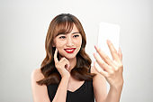 Portrait of a happy asian businesswoman using mobile phone isolated over white background