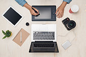 Graphic designer working with digital tablet at desk. Top view.