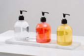 Cosmetic bottles with shower gel, body lotion or shampoo and bath towels. Bathroom accessories.