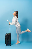 Positive asian female pictured isolated on background with suitcase and tickets for plane dancing with joy of upcoming journey