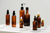 Spa cosmetics in brown glass bottles on gray concrete table. Copy space for text. Beauty blogger, salon therapy, branding mockup, minimalism concept