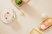 Modern gold stylized home office desk with folder, macaroons, coffee mug on beige background. Flat lay, top view lifestyle concept.