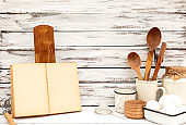 Vintage old baking kitchenware and recipe book on white wooden background.