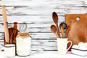 Vintage old baking utensils on a white wooden background.