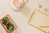 Women's home office workspace with clipboard, macaroons, pen, coffee mug on pastel background. Flat lay, top view lifestyle concept.
