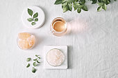 Aromatherapy. Small glass bottles with cosmetic oils. Bath salt. Fresh leaf. Objects for spa procedures on white background oil, leaf.