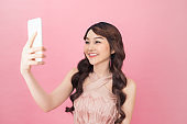a beautiful young asian woman dressed in pink dress posing while standing and taking a selfie