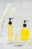 bottle of aroma essential oil with orchid on table, spa concept.