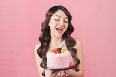 Joyful woman with cake front pink background