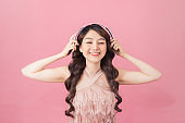 Happy cheerful Asian woman wearing wireless headphones listening to music on pink background