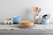 Cooking pancakes. Shrovetide (Maslenitsa) - blini stack on a blue plate on a wooden table.