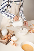 Mixing white egg cream in bowl with motor mixer, baking cake