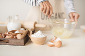 Young man's hands whisk eggs with sugar to bake fruit cake. Male cooking dough for pie on white table