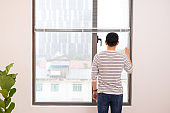 Man relaxing in his chair and enjoying the view from living room window