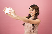 Studio portrait of beautiful woman smiling with white teeth and making selfie, photographing herself over pink background