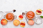 Homemade peach jam with organic fruit. Sweet preserves on a light background, copy space