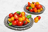 Colorful organic cherry tomatoes on silver plates, light background.
