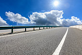Asphalt road and blue sky with white clouds