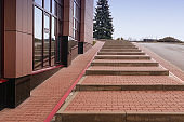 Stairs on the street near the business center. Large steps to the top of the rise. Wide staircase to climb the hill next to the office building.