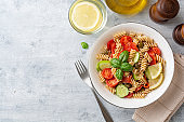 Whole wheat pasta salad with cucumbers, cherry tomatoes, salted salmon and capers on concrete background
