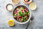 Healthy pearl barley salad with beans, cucumbers, red onion, sunflower seeds, pomegranate and parsley in bowl on concrete background
