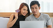 Asian Couple shopping online and paying with credit card at laptop computer,Happy couple at home surfing the net in bed