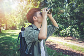 Asian Group of young people Hiking with friends backpacks walking together and using binoculars ,Relax time on holiday concept travel