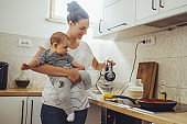 Single mother working at kitchen. Young mother making pancakes.