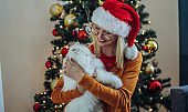Young woman and white persian cat in front of christmas tree