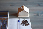Keys, calculator, house model, notebook and pen